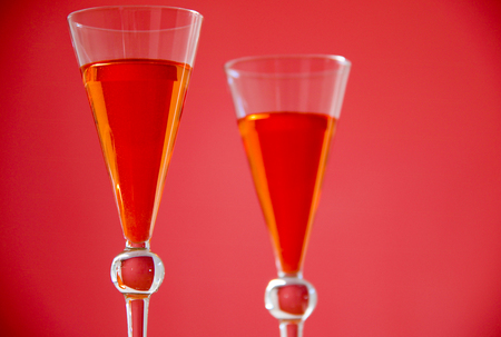 selective focus on two fresh orange cocktails on red background.