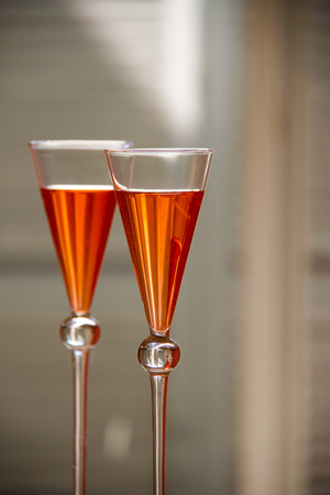 two elegant orange cocktails with multicolored reflections in the glass Stock Photo