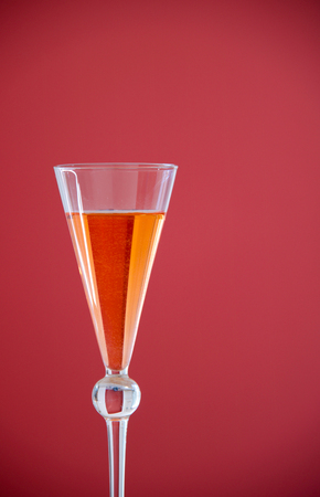 close up of a  beautiful glass with conical shape of orange cocktail.