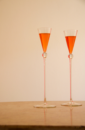 beautiful vintage glasses for two orange cocktails, beige background