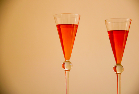 close up of two vintage glasses of orange cocktails, pale yellow background