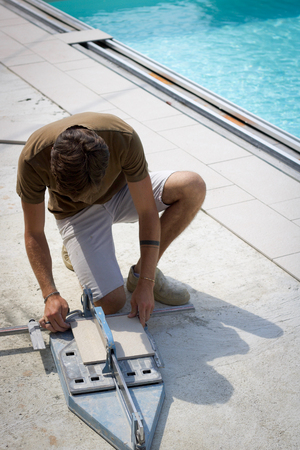 young tiler working cutting a tile for flooring near a swimming pool