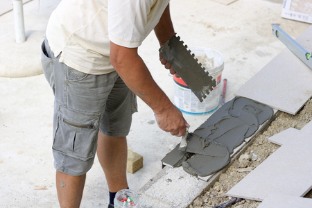 tiler spreads the glue with the trowel to lay the tiles