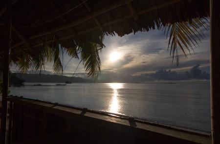 beautiful exotic sunrise from a wooden balcony on the beach, raja ampat archipelago