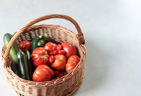 wicker basket full of fresh tomatoes and  zucchini on grey background Stock Photo