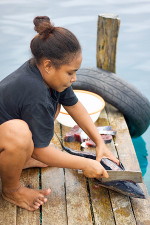 RAJA AMPAT, WEST PAPUA - August 31,  2017: asian young girl prepare tuna fillets on the dock for lunch and throw waste to sharks in the sea