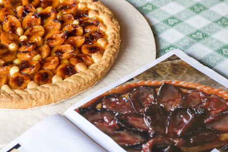 prunes tart near a notebook of recipes on the table