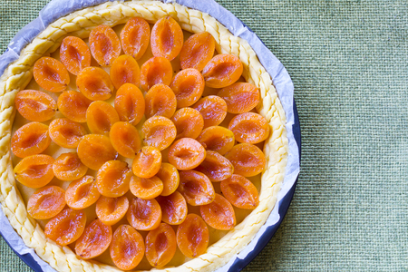 prunes tart beefore baking decorated with fresh fruits on green tablecloth