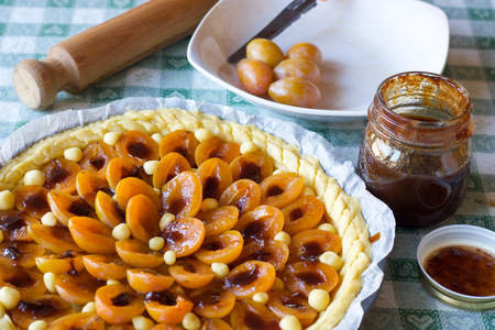 close up of preapartion of prunes tart with fresh fruits and marmalade