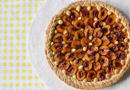 close up of plums tart with fruits and marmalade on the yellow squares tablecloth