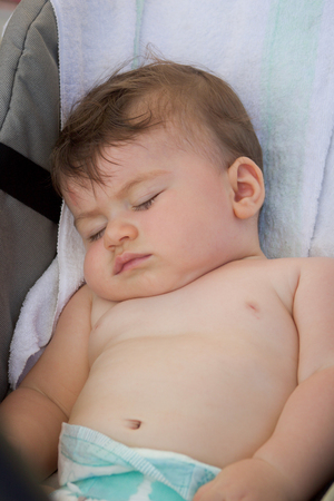 adorable baby boy sleeping naked  on the stroller in summer