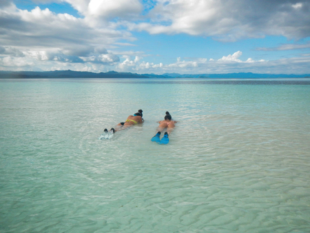 two girls in bikini lying in the water ready for snorkeling in west papua Editorial