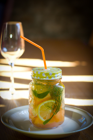 glass jar  of flavored fruits water on wooden table, copy space
