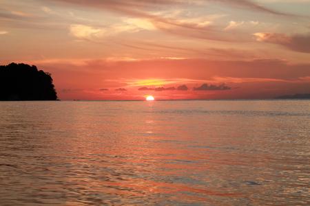 excepcional puesta de sol tropical en el mar con tonos rojos en el cielo, islas togian Foto de archivo
