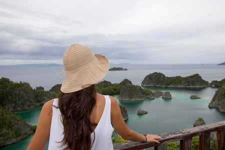 beautiful young woman with cotton hat back in front of typical west papua  seascape Stock Photo