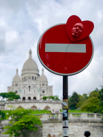 selective focus road sign in front of  sacre-coeur basilica in paris