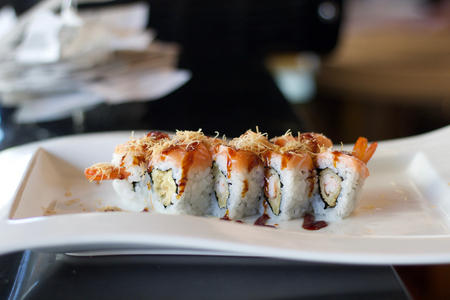 close up of sushi rolls with shrimp and salmon on white plate
