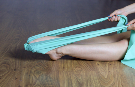 female legs doing exercices for feet strengtening with elastic band sitting on wooden floor