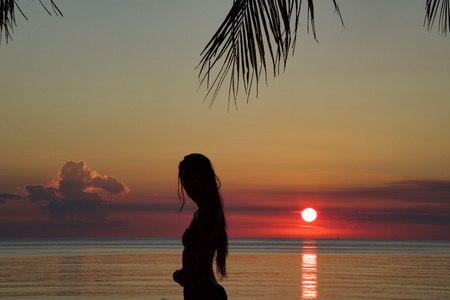 silhouette of young woman standing on the beach in bikini at  sunset on kalimantan, Borneo