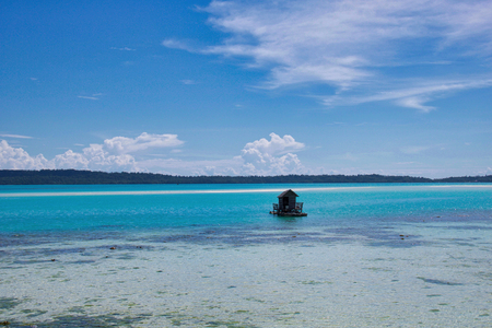 beautiful exotic seascape with a little fisherman house in turqouise water, indonesian borneo