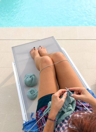 woman sitting on a sunbed near a swimming pool knitting a green sweater, view from above, vertical, copy space