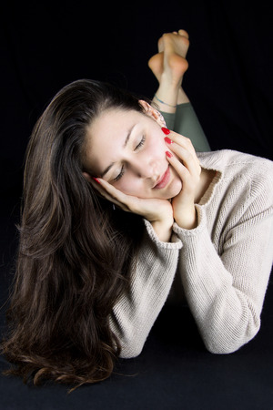 beautiful young woman with closed eyes  lying down with cachemere beige sweater, black background Stock Photo