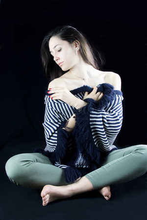 young girl sitting  on black background covering her body with a wool striped cape