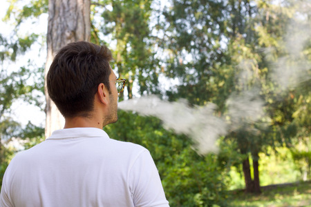 young man emitting steam from the electronic cigarette, garden background defocused