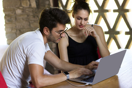 young couple sitting on a wooden table looking and writing on laptop Stock Photo