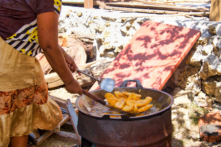 woman cooking fried bananas along the street of a small village, indonesia, borneo island