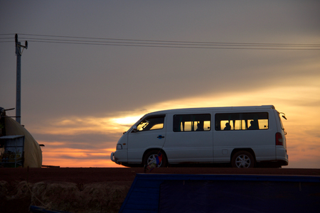 white minibus at sunset on a  dirt road, kampong plug, cambodia