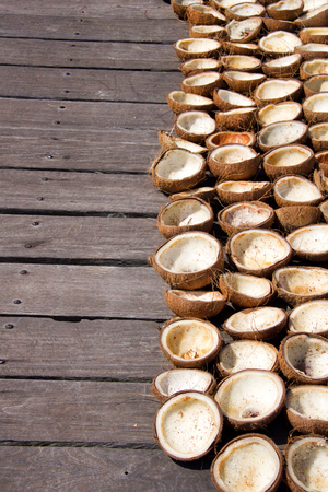 coconuts cut into half on a wooden pier drying in the sun to make coconut oil, Indonesia, copy space Stock Photo