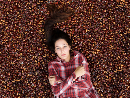 portrait of a beautiful woman in scottish dress lying down on chestnut carpet, copy space