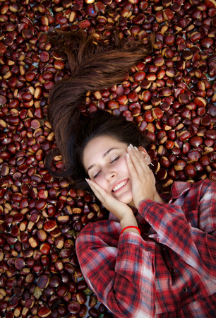 portrait of beautiful woman smiling with closed eyes lying down on chestnut carpet Stock Photo