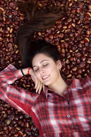 beautiful fashion model in scottish red shirt lying down on chestnut carpet Stock Photo