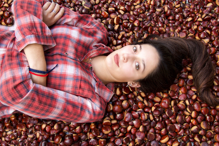 beautiful model with long hair in scottish dress lying down on moltitude of chestnuts