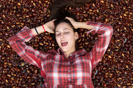 beautiful girl playing and smiling with closed eyes laying down on chestnut carpet