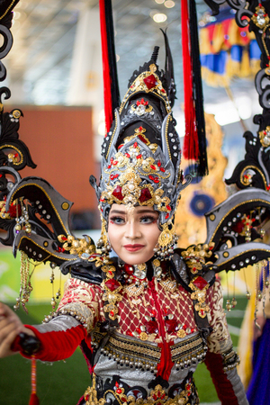 JAKARTA - September 5, 2018: portrait of beautiful woman in south east asia  traditional cerimonial costume  red , gray and black with precious stones during a parade