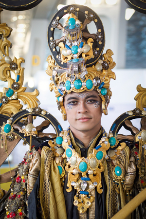 JAKARTA - September 5, 2018: portrait of handsome boy in south east asia  traditional cerimonial costume with  gold and precious stones during a parade