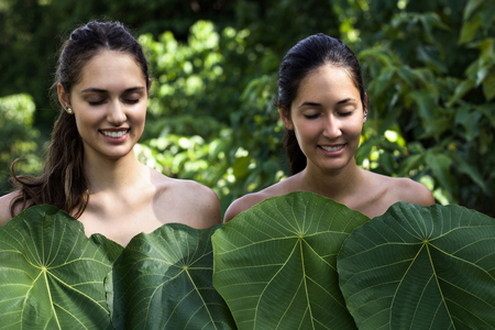 two beautiful smiling girls in the jungle covered by large green leaves Stock Photo