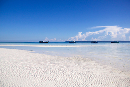 beautiful beach in kalimantan with low tide and four berthed boat, borneo island