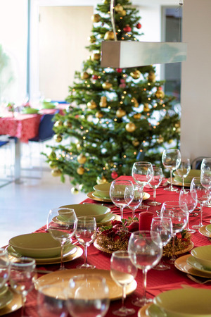 table settings for christmas lunch and christmas tree on the background