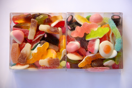 close up of two transparent boxes of multicolored jujubes on lilac background