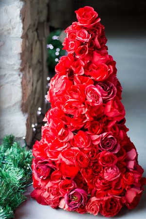 christmas tree made by a large group of red paper roses near a window