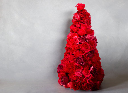 unusual christmas tree made by red paper roses isolated on gray Stock Photo