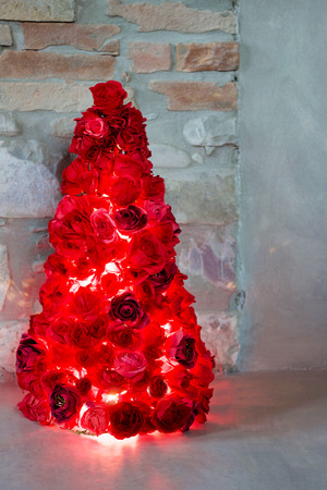 christmas tree made by red paper roses illuminated, on the floor, stone wall background Stock Photo
