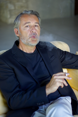 adult man in white beard wearing a blue jacket smoking on a yellow sofa