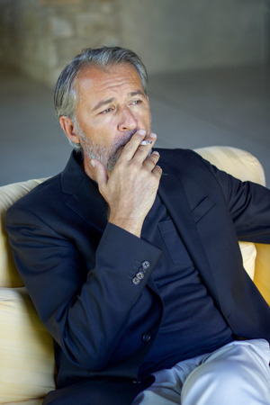 handsome adult man wearing blu jacket sitting and smoking on a yellow sofa