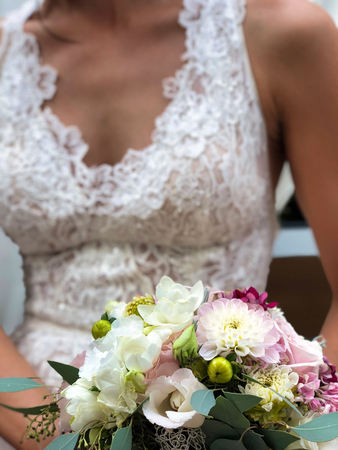 focus on a bridal bouquet in the hands of a bride, wedding symbol