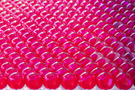 group of lined  shiny hydrogel balls in vivid fuchsia color Stock Photo